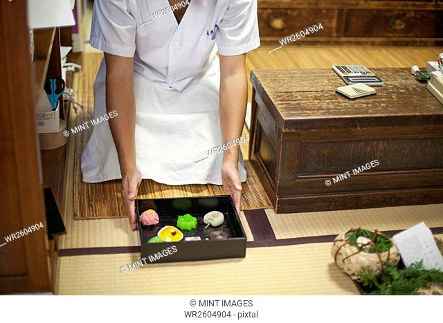 A small artisan producer of specialist treats, sweets called wagashi. A chef presenting a tray of selected wagashi of different shapes and flavours