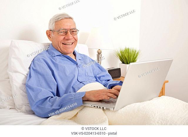 Senior man using laptop, lying in bed