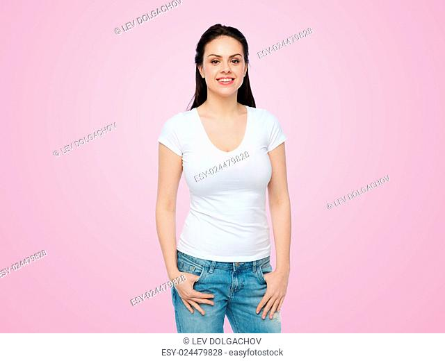 advertisement, clothing and people concept - happy smiling young woman or teenage girl in white t-shirt over pink background