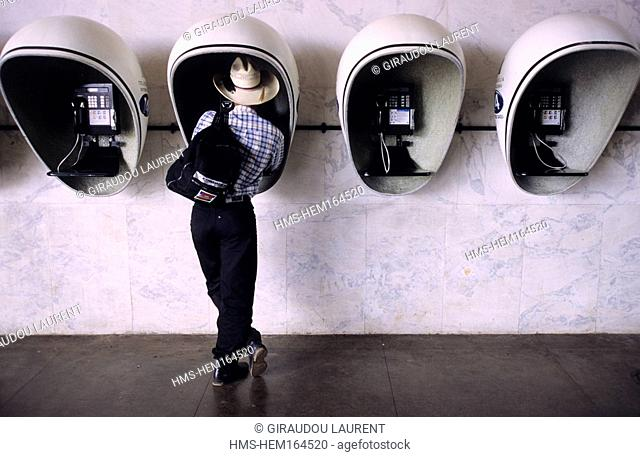 Brazil, Brasilia, city of the future, central bus station, public phones, man at phone booth