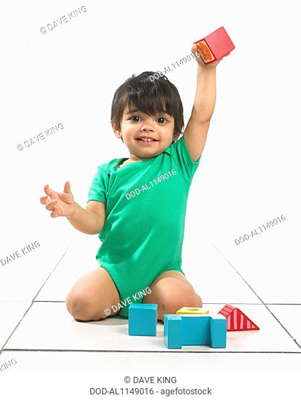 Boy (16 months) playing with colourful blocks