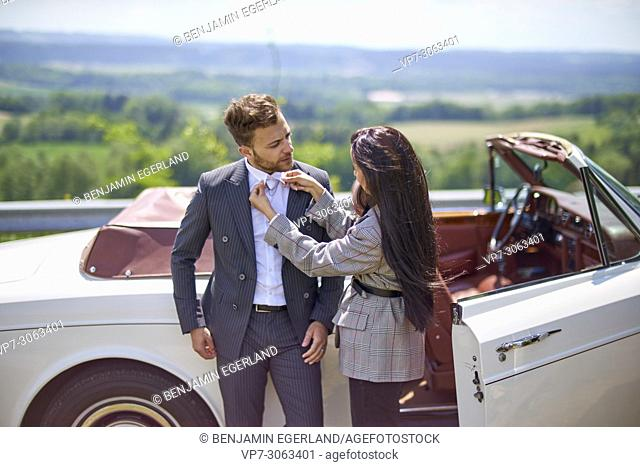 woman fixing shirt of man in front of luxury car. Turkish ethnicity. High society. Blogger Adem Bayalan. Bavaria, Germany