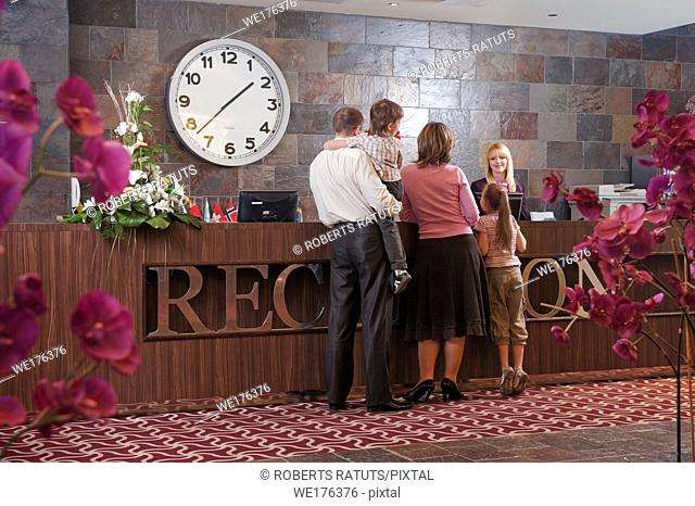 Happy family checking in at the reception desk