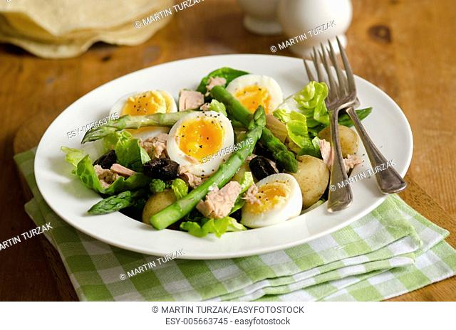 Salad made of tuna, boiled eggs, potatoes, asparagus and black olives