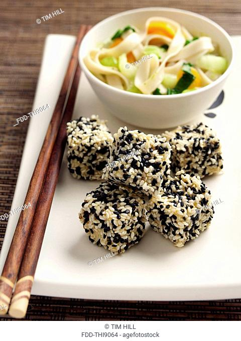 Deep fried tofu coated in black and white sesame seeds rice noodles stir fried vegetables carrots scallions sugar snaps Japanese main meals