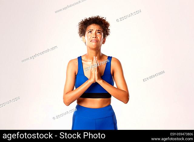 Concept of sport and workout. Desperate african-american fitness woman pleading God, holding hands in pray and begging, looking up with sad face