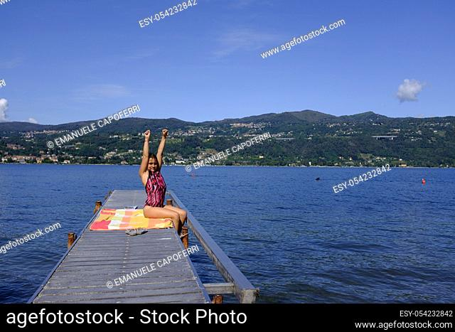Girl stretches on the pier, Lake Maggiore, Ranchi, Lombardy, Italy