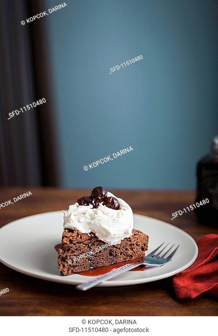 Gluten-free chocolate cake with cream and cherries