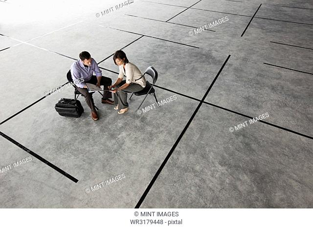 Caucasian business man and woman looking at plans for a new office layout in a large empty raw office space