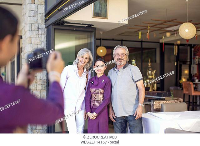Senior couple taking pictures with Asian waitress in front of restaurant