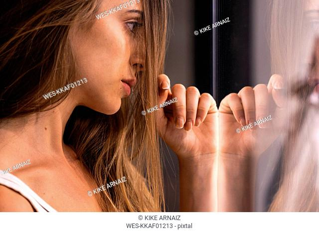 Serious attractive young woman leaning against glass pane