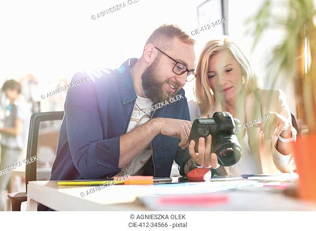 Photographer design professionals using SLR camera in office