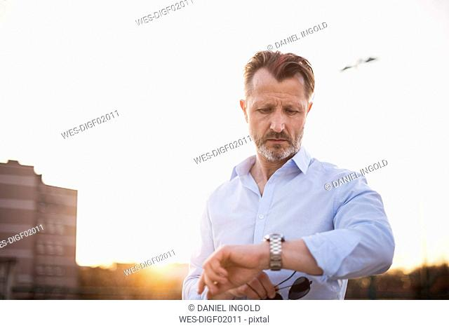 Portrait of mature man checking the time