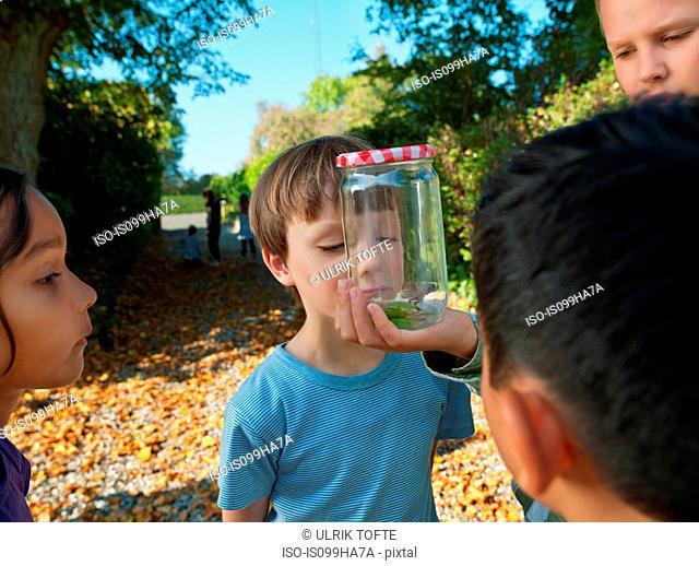 Boy showing jar to children