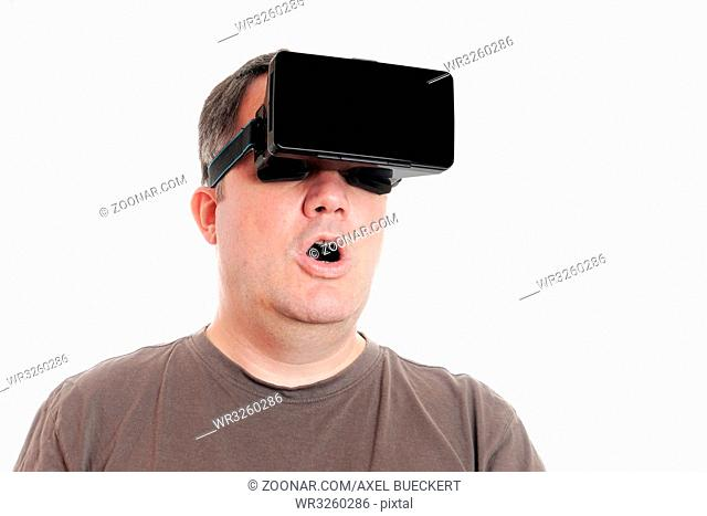 middle aged man wearing virtual reality headset is stunned by VR experience