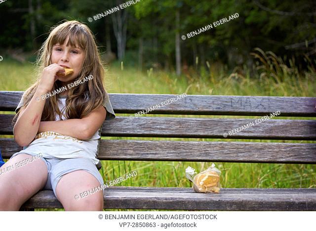 Young girl enjoying break on bench while eating rusk