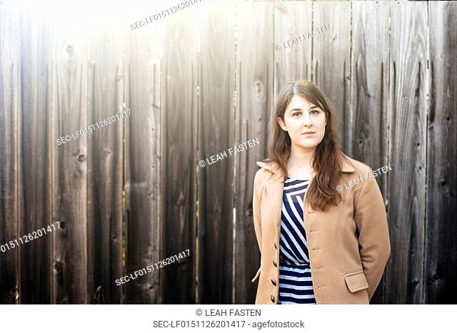 Portrait of young woman standing in front of wooden fence