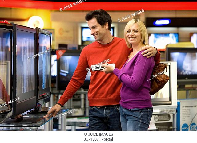 Young couple shopping for television, smiling, portrait of woman