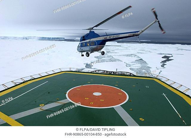 Helicopter with tourists, taking off from heli-deck on 'Kapitan Khlebnikov' icebreaker, on route to view Snow Hill Island Emperor Penguin colony, Weddell Sea