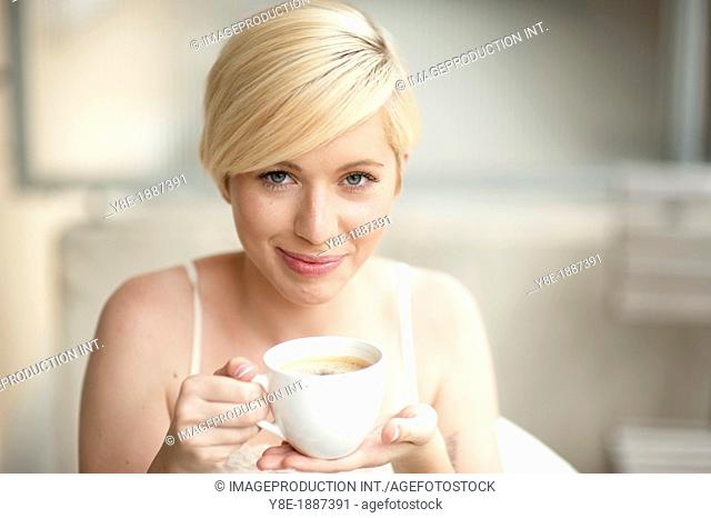 Czech Republic, Portrait of young woman holding cup of coffee