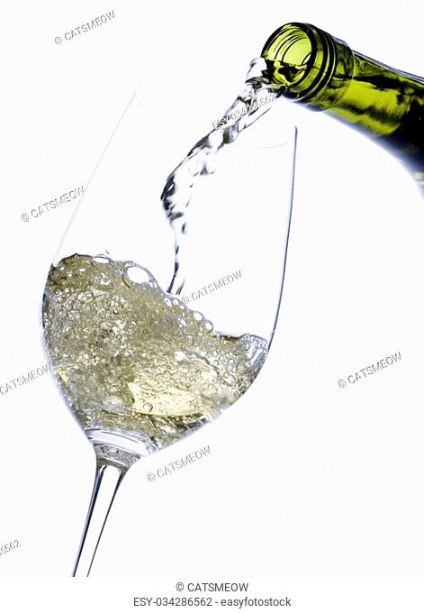 White Wine Poured into a Glass Isolated on White