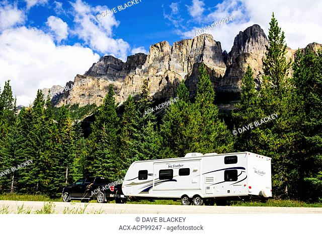 A truck and trailer parked along the Bow Valley Parkway near Banff, Alberta. Castle Mountain is in the background