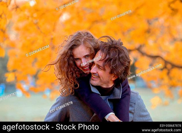 Couple in autumn park having fun, smiling man carrying woman piggyback outdoor