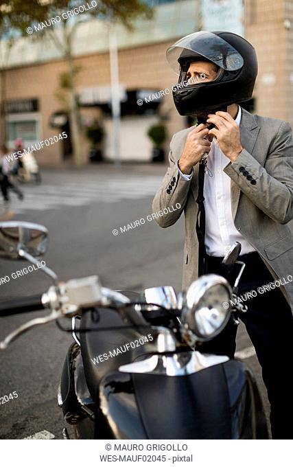 Businessman next to motorscooter putting on helmet