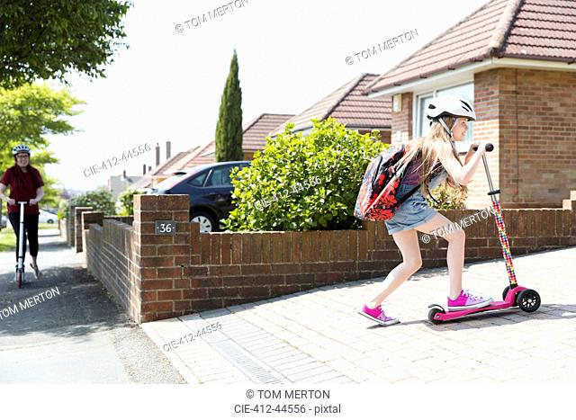 Girl riding scooter in sunny driveway