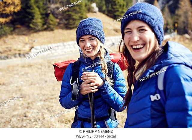 Two laughing young women hiking in the mountains