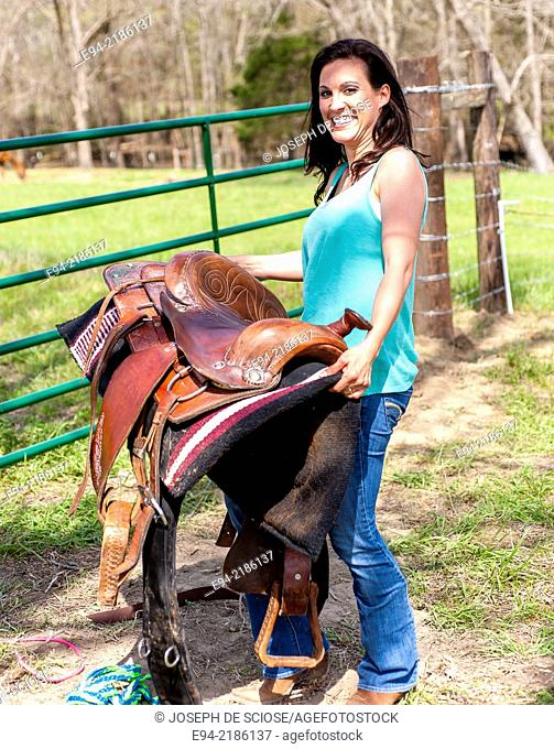 A 36 year old brunette woman carrying a saddle in a pasture