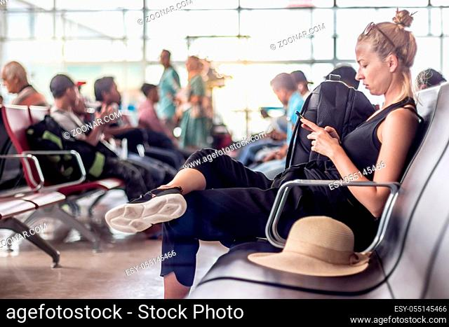 Casual sporty young blond female traveler using her cell phone while waiting to board a plane at the departure gates at the asian airport terminal