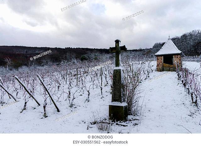 Religious cross in winter snowy vineyard, Alsace, France