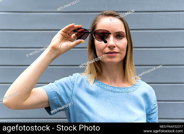 Blond woman looking through sunglasses while standing in front of wall