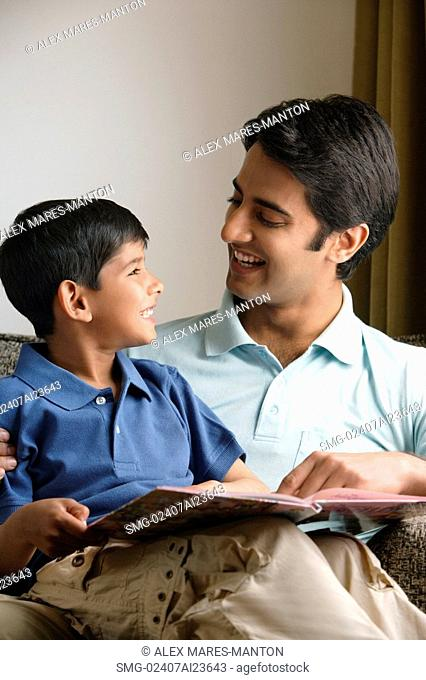 father and son smiling at each other, story book