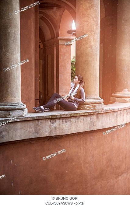 Young woman wearing sports clothes sitting resting