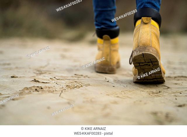 Spain, Navarra, Bardenas Reales, hiking shoes of young woman walking in nature park, close-up