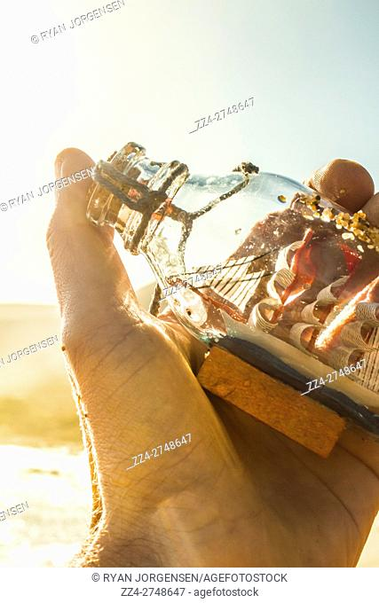 Creative portrait on the hand of a sailing man holding a nautical glass bottle with captive boat. Capturing the ocean