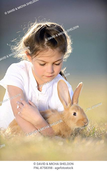 Girl with her rabbit on meadow, Upper Palatinate, Bavaria, Germany, Europe