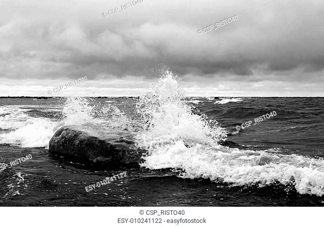 White waves hit a big rock in the sea