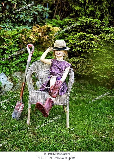 Smiling girl on wicker chair in garden