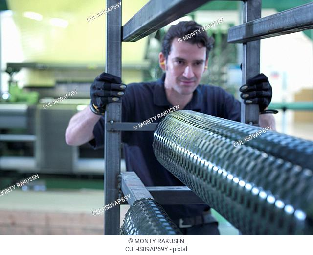 Worker operating carbon fibre loom in carbon fibre factory