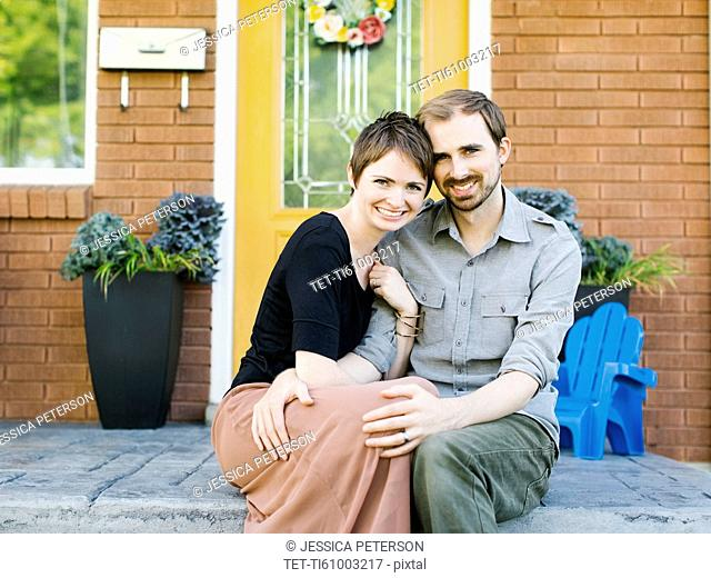 Happy couple sitting in front of house