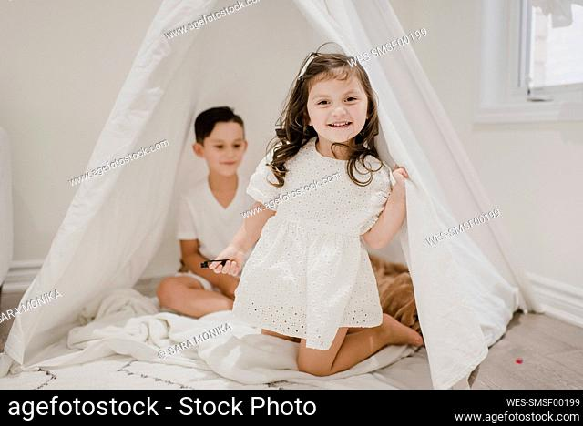 Smiling sister with brother kneeling in tent at home