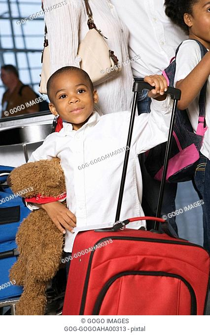 African boy holding suitcase