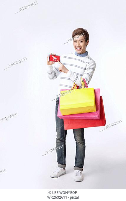 Young smiling man with shopping bags standing showing smartphone