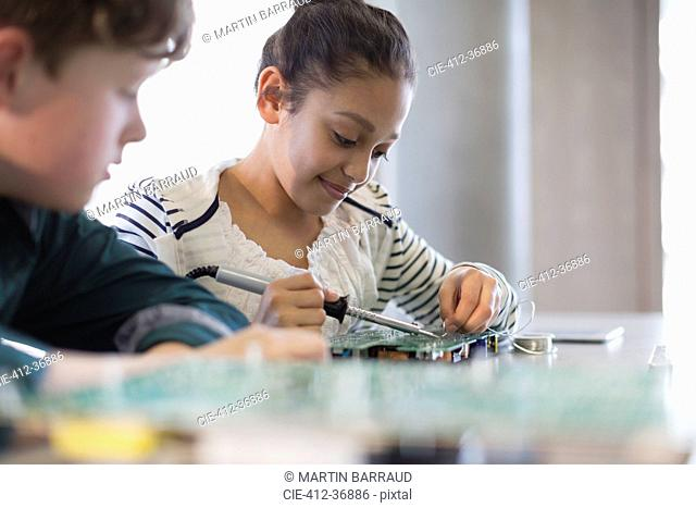 Students soldering circuit board in classroom