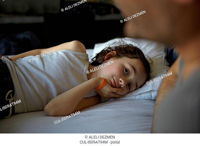 Girl lying on bed watching father