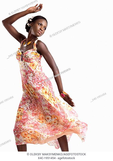 Beautiful young black woman dancing in a pink floral summer dress isolated on white background
