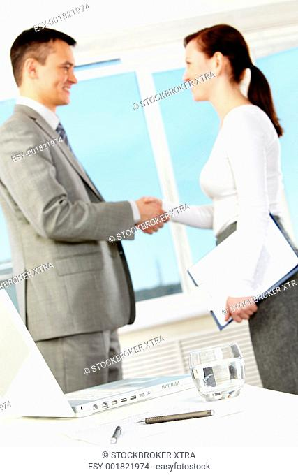 Photo of business objects at workplace with business partners handshaking after making agreement